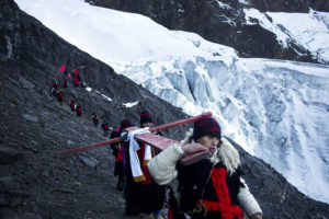 "In this May 24, 2016 photo, men dressed as mythical half-man, half-bear creatures called ""Ukukus"", descend the Qullqip'unqu mountain glacier carrying a cross on the last day of the syncretic festival Qoyllur Rit'i, translated from the Quechua language as Snow Star, in the Sinakara Valley, in Peru's Cusco region. The ukukus also used to cut away blocks of ice from the glacier to bring down to share with the community in the belief that the melted held magical healing powers, but no longer noting a decline in the size of the glaciers because of warming trends. (AP Photo/Rodrigo Abd)"