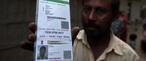 Faizul Islam hold his son Abu Hanif's ID card. His son was one of the teenagers beaten to death by a mob.